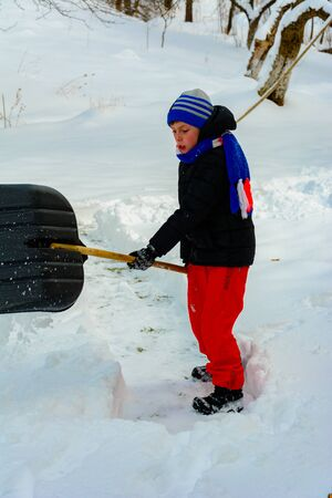 Cleaning snow in winter, the boy shovels snow. 2019