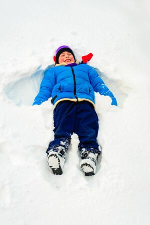 A boy in white fluffy snow makes an angel. 2019