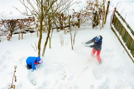 Two brothers playing snowballs near their home.2019
