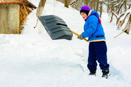 After heavy snow, the little boy clears the snow with a shovel. 2019 Zdjęcie Seryjne