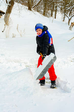 The boy shovels the snow near his house in winter. 2019