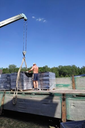 Workers in the village unload pallets with a front brick for construction with the help of a mobile crane.