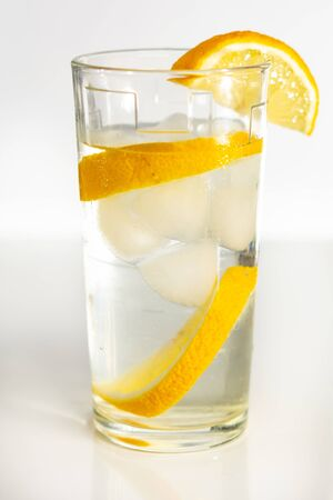 Glass of cold water with slices of ice and lemon. 2019
