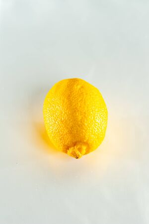 Faded stale lemon on a white background close up.