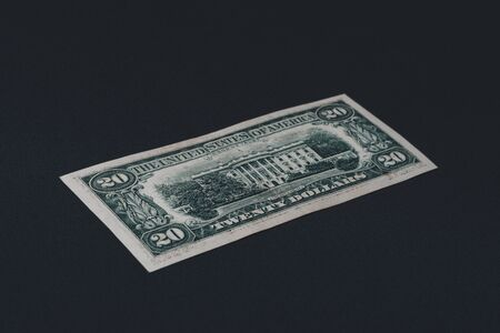 Close up of twenty dollars lie on the back on a black background.2019