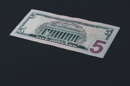 The American five dollars lie on the back on a black background. 2019