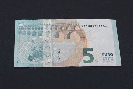 Detail of 5 euro banknote with anti-counterfeiting holograms, Selective focus, black background, one banknote. 2019
