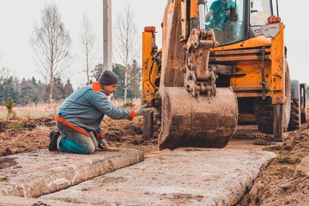 The excavator installs concrete slabs for the road. 2019 Stock Photo