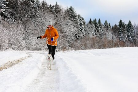 young woman runner training in winter park with husky dog.2020