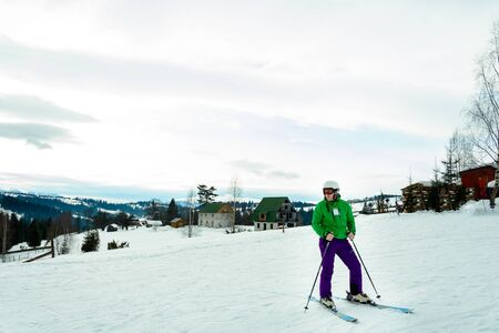 Young man in green jacket and purple pants skiing. 2018 Foto de archivo - 138299663