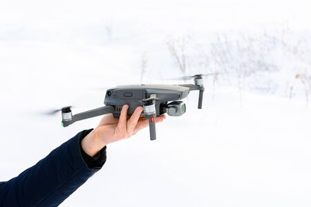 A young man launches a drone into the air in winter in the forest. 2020