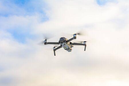 Kleine graue Drohne, die in den Himmel fliegt, Quadcopter auf einem bewölkten Himmelshintergrund.2020