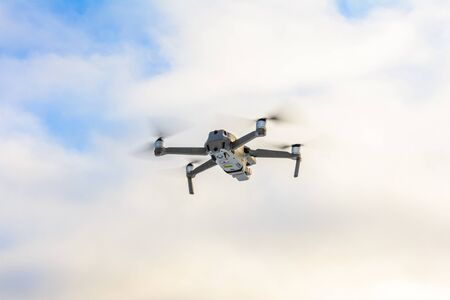 Small gray drone flying in the sky, quadcopter on a cloudy sky background.2020