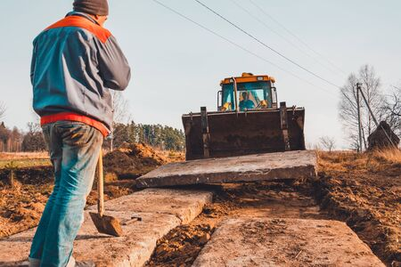 The yellow excavator transports concrete slabs in the countryside 2020
