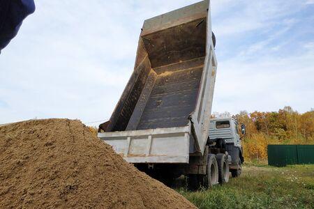 A dump truck unloads sand at a construction site to mix cement.2020