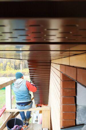 A man trims a curtain rod with an angle grinder.2020