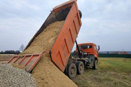 A dump truck unloads sand at a construction site.2020