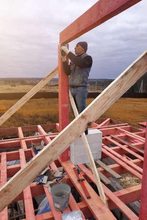 Joiner on roof installation, hammer hammering nail into wooden beam.2020 Imagens