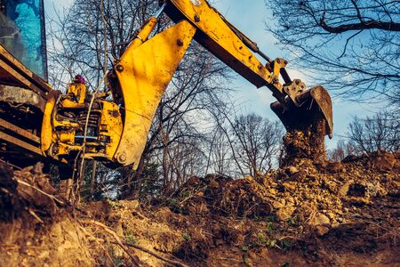 The excavator performs excavation work by digging the ground with a bucket in the forest.2020