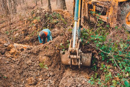 An excavator in the forest digs a ladle for fish breeding. 2019