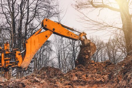 A yellow old excavator in the middle of the forest digs a ladle pit to collect water.2020