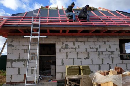 Workers cover the roof with insulating material, insulate it from cold and water.2020