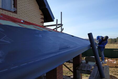 The worker covers the roof with thermal insulation material, waterproof film.2020