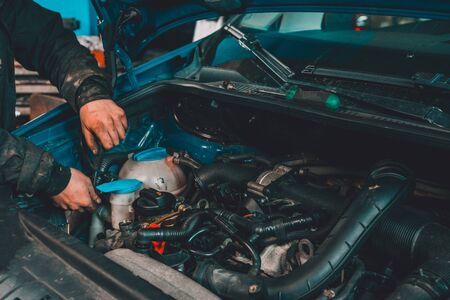 the master repairs the engine in the car service during a malfunction 2020