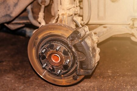 Car brake disc closeup on car service lifted for replacement 2020 写真素材