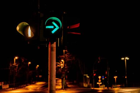 Closeup of colorful traffic lights with arrows in night city 2020