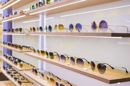 Storefront shelves of various modern sunglasses at the airports retail store 2020