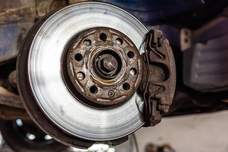 Car brake disc closeup on car service lifted for replacement 2020 Archivio Fotografico