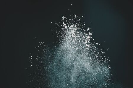 Wonderful pattern of white powder of light snow and flour explodes on black background 2020