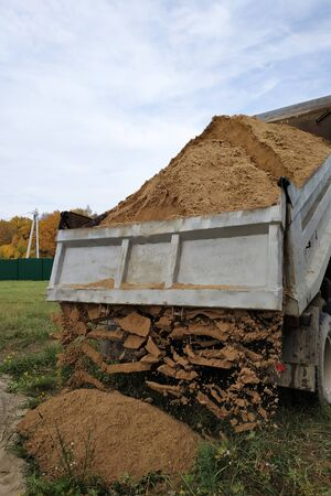 A dump truck unloads sand in the construction site.2020