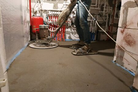 The worker with special tools performs sand-cement screed for heating and floor heating.2020