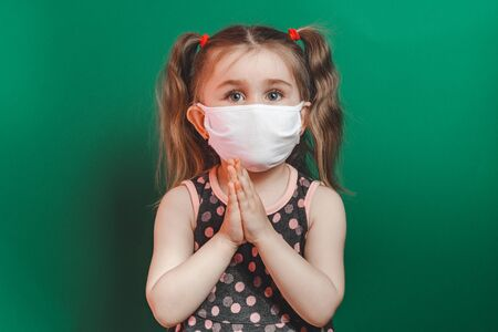 Caucasian sick little girl in medical mask during coronavirus epidemic prays on green background.