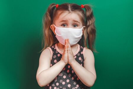 Caucasian sick little girl in medical mask during coronavirus epidemic prays on green background closeup 2021 스톡 콘텐츠