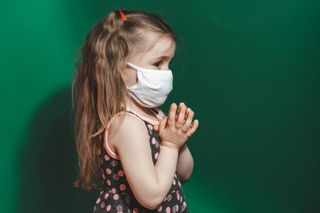 Caucasian sick little girl in medical mask during coronavirus epidemic prays on green background closeup..