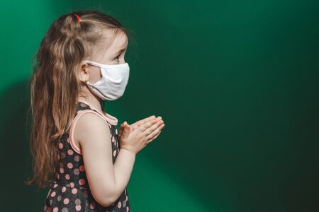 Caucasian sick little girl in medical mask during coronavirus epidemic prays on green background closeup.Copy space.