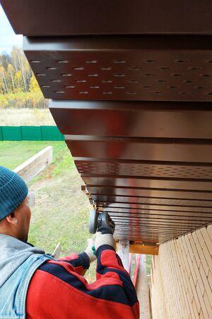 A man trims a curtain rod with an angle grinder.