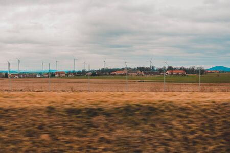Windmills far in field in countryside of Poland from car window 2020