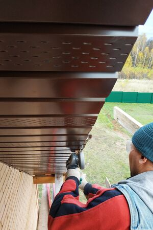 Worker trims the metal sheet of the roof.2020