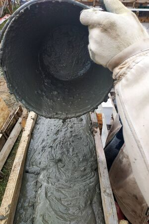 The worker pours a bucket of cement into the formwork.2020 Reklamní fotografie