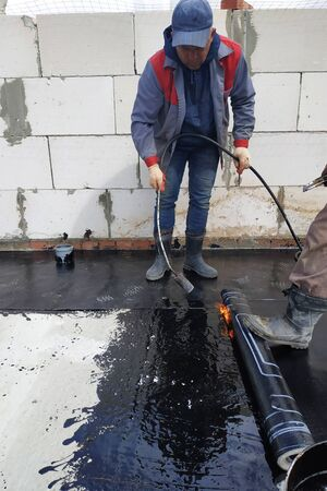 A waterproofing specialist with an assistant melts the bituminous resin with a blowtorch and seals a reliable roll material. Hermetic covering of roofs and walls at a waterproof 2021.