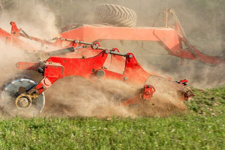 Agricultural equipment shreds the plowed land. A crawler tractor pulls a harrow to loosen the soil close up 2021.