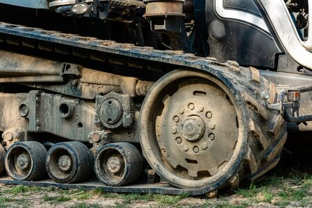 Tractor caterpillar on an agricultural field close up. A modern new tracked tractor is very close. 스톡 콘텐츠