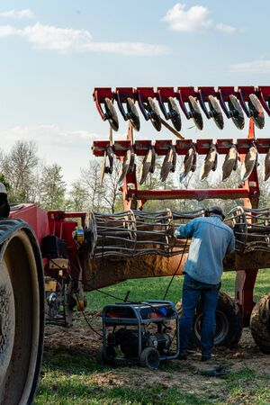The farmer repairs the harrows if they are damaged by hitting stones. A master welder welds metal parts of agricultural equipment 2021.