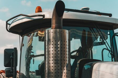 Catalytic converter tractor and cab with large windows close up on a background of blue sky. Exhaust pipe of a modern new bulldozer.