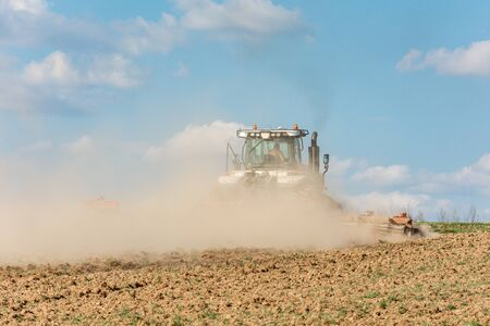 In the spring, a farmer pulls harrows with a modern tractor and sows a field with beets. Sowing campaign on agricultural land during tillage 2021. Standard-Bild