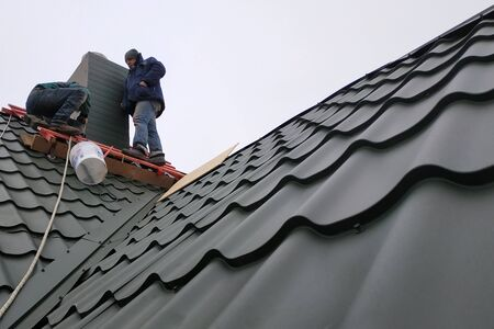 Working with roofing material, metal roof, hand tools screwdriver.2020 Stock Photo